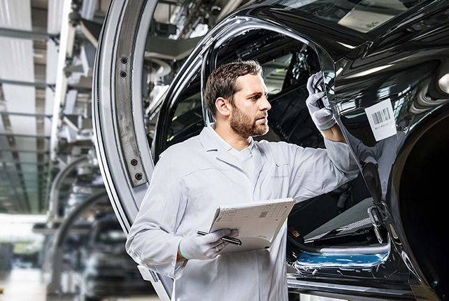 A man inspects a Volkswagen in the Glass Factory