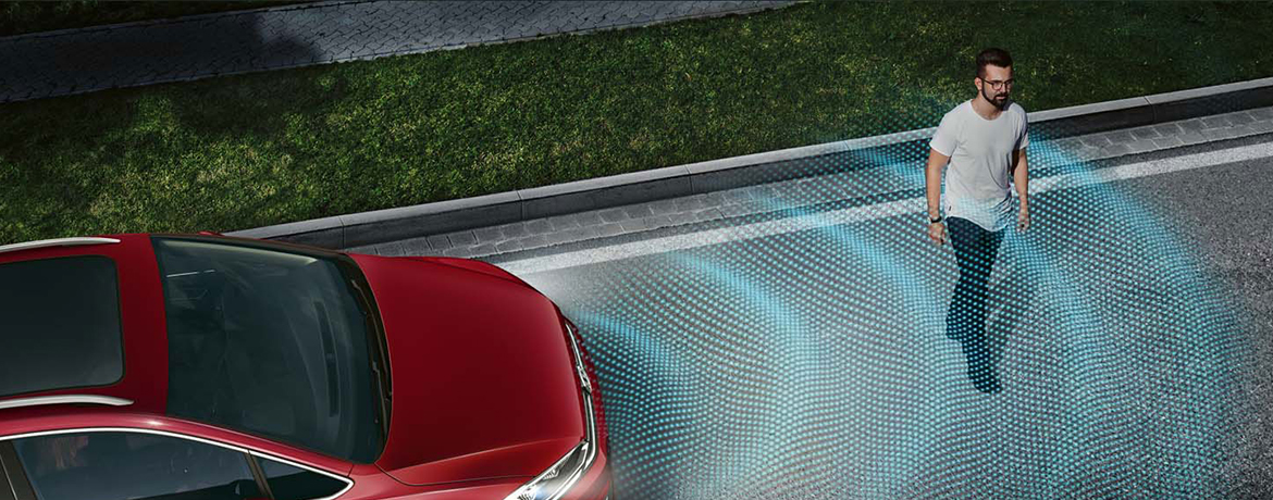 A vehicle's sensors detect a pedestrian crossing the road.