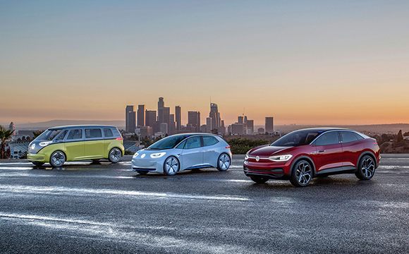 Three Volkswagen IDs with a city skyline as a backdrop, photographed at sunset.