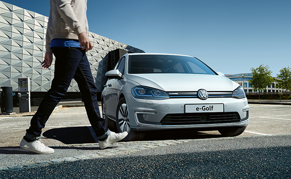 A person walking towards a parked e-Golf