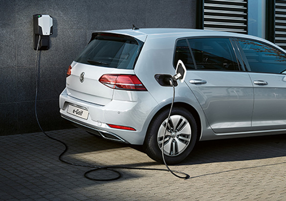 An e-Golf is being charged by a wall panel