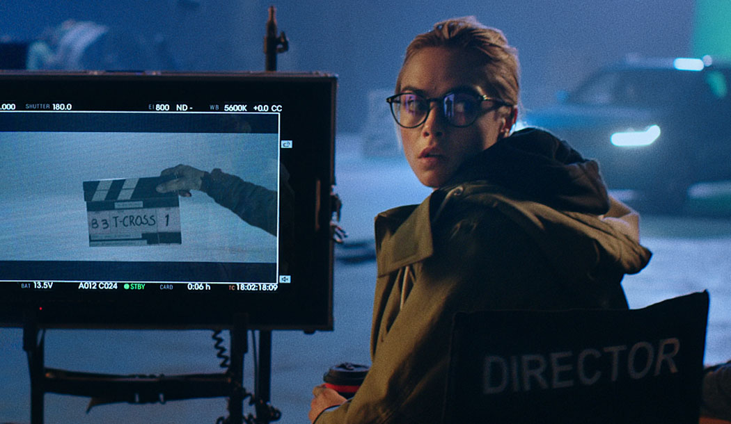 Cara Delevingne sitting in a Director's chair looking over a monitor with a T-Cross director's board on it.