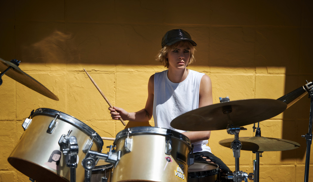 Cara Delevingne playing the drum set.