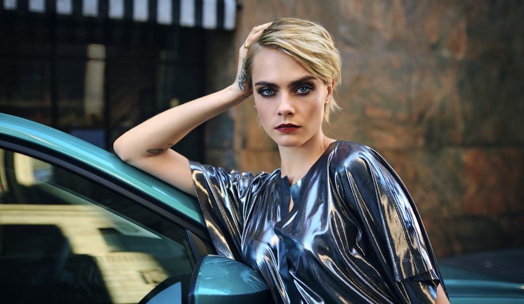 Cara Delevingne resting her head on her hand while standing alongside the new T-Cross.