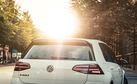 The rear of an e-Golf in front of a setting sun.