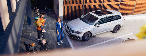 A family standing around their new Passat GTE as it charges
