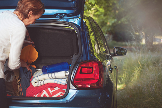 A woman takes things out of the boot of a Volkswagen