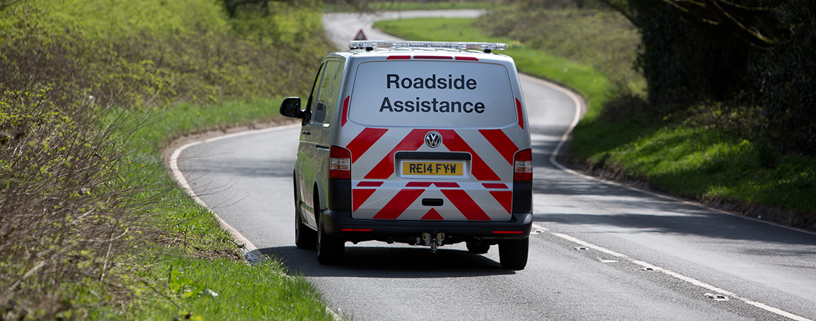 A Volkswagen Roadside Assistance van drives away into the distance along a country road