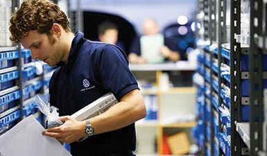 a Volkswagen mechanic looks for parts. Genuine Parts