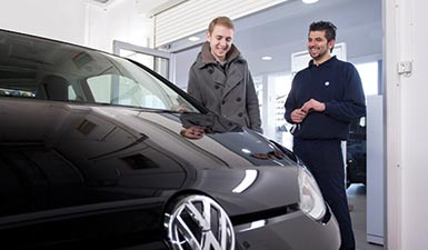 A man smiles at his repaired Volkswagen. He is happy that it has been repaired and shares a laugh with the man who has fixed it.