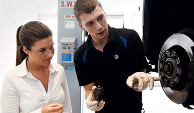 A Volkswagen mechanic shows a customer how the brake works