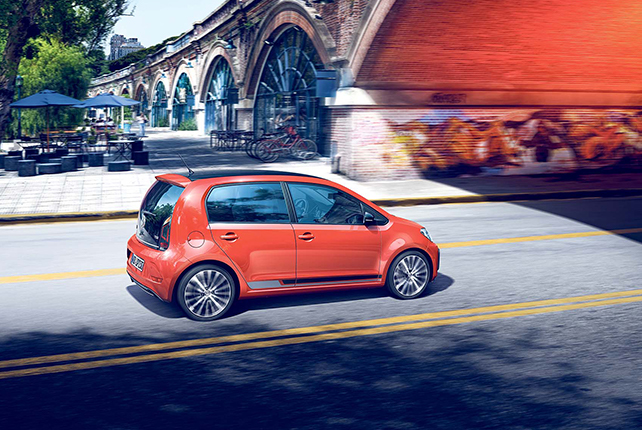 A red Volkswagen up! drives along