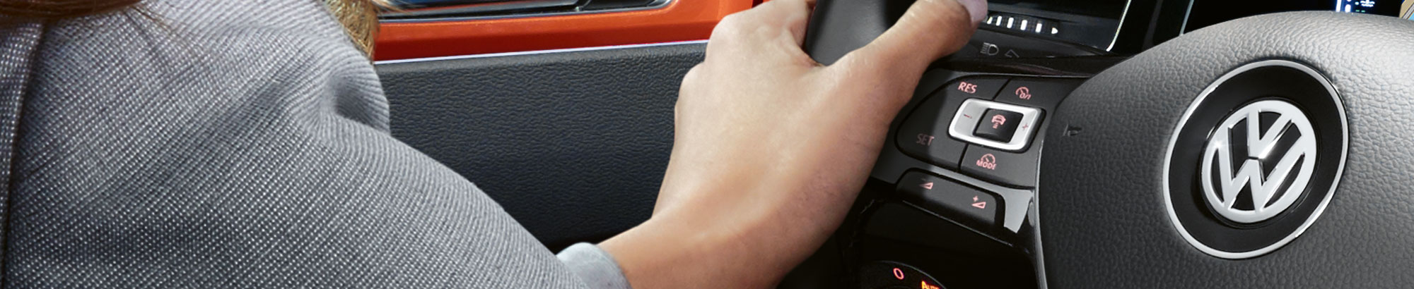 Hand resting on a VW steering wheel console
